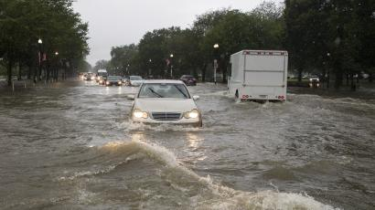 Water up to car headlights on roads in downtown Washington DC.