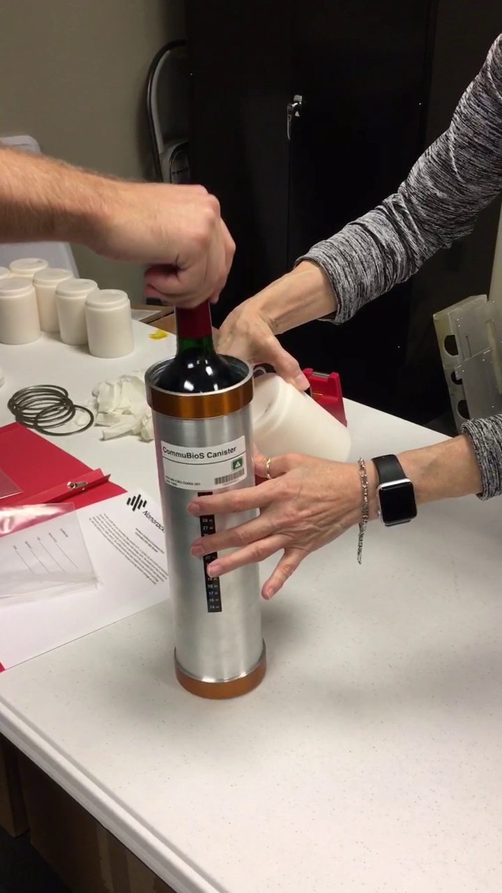 A canister is loaded with a wine bottle for a trip to the International Space Station.