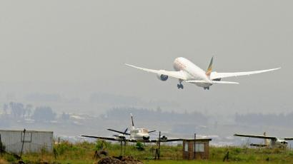 An Ethiopian Airlines plane takes off into a smoggy sky.