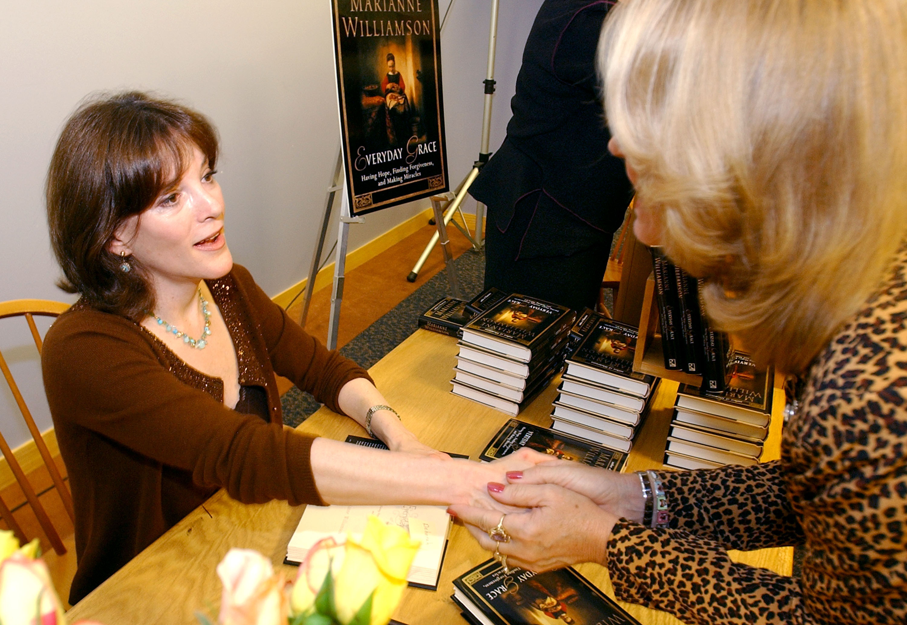 Marianne Williamson signs books and meets a fan in 2002.