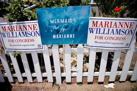 """Marianne Williamson for congress signs, including one that says """"Mermaids for Marianne"""""""