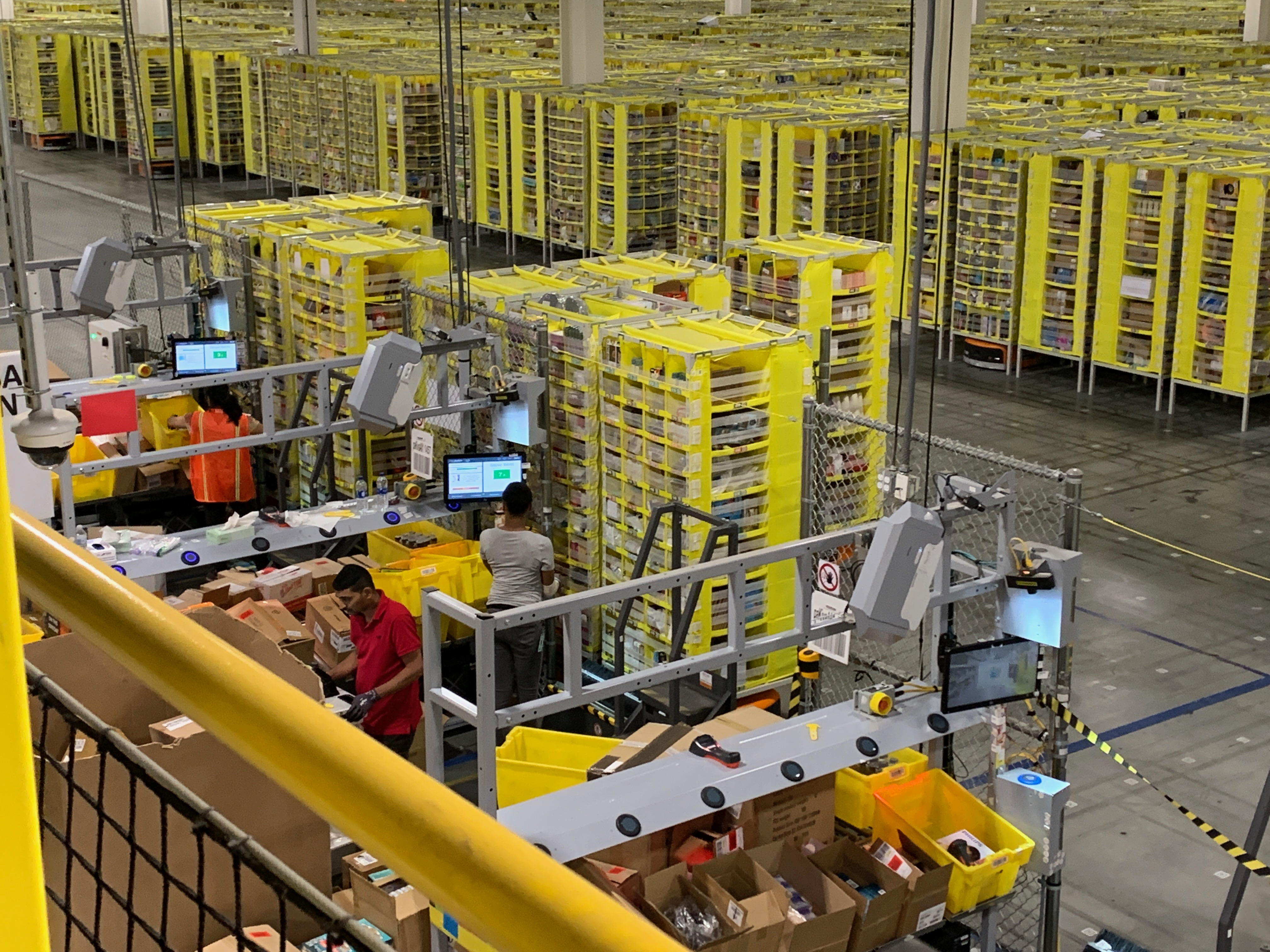 Amazon workers sorting products, randomly, into shelving towers