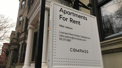 A Compass for-rent sign hangs on a townhouse in Brooklyn, New York.