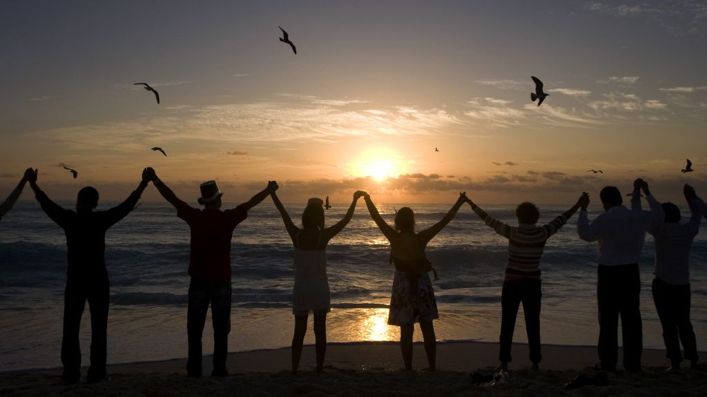 People raise their arms to welcome the first rays of sunshine of the new year on Playa Delfin in Cancun, Mexico