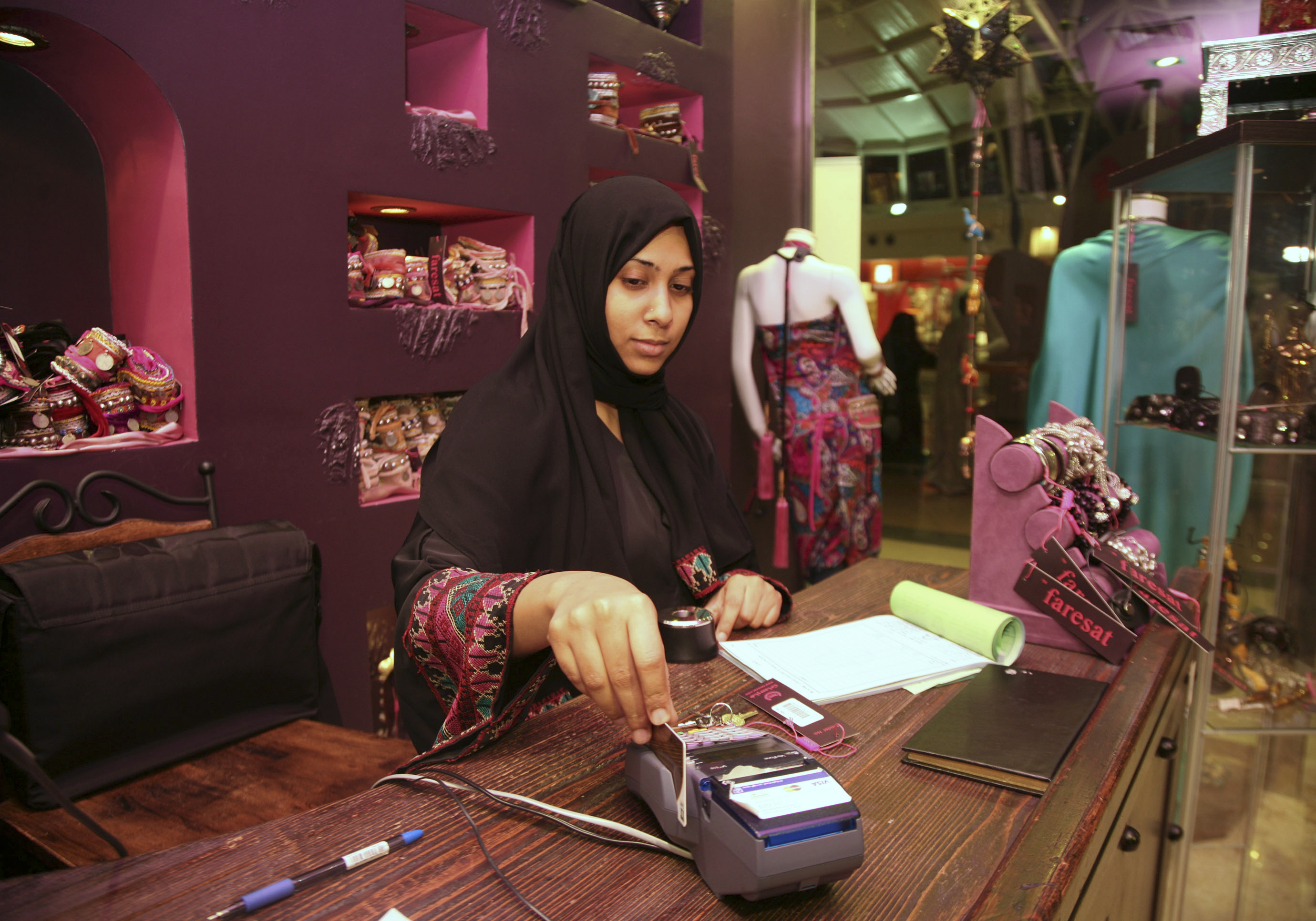 A Saudi saleswoman works in a boutique at a mall in Jeddah January 9, 2012. In a country where women are banned from driving and need the permission of a close male relative to work, travel and even have certain kinds of surgery, female employment is another battleground between traditionalists and those who want change. Women account for only 7 percent of Saudis employed by private companies but make up almost half of all Saudis listed as looking for work, according to 2009 government figures. Picture taken January 9, 2012.