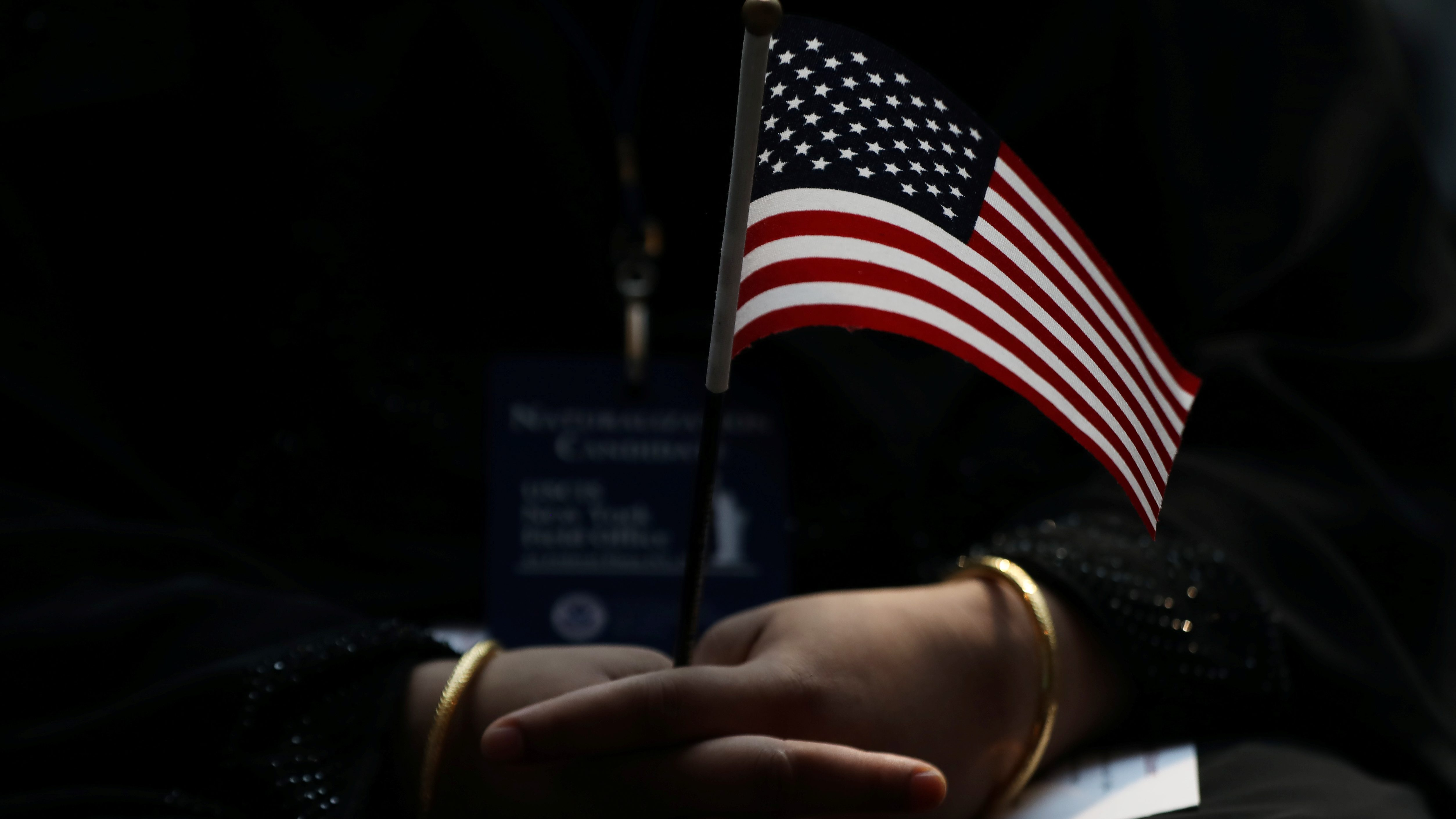 An immigrant woman holds a U.S. flag during a U.S. Citizenship and Immigration Services Naturalization ceremony in the New York Public Library in New York