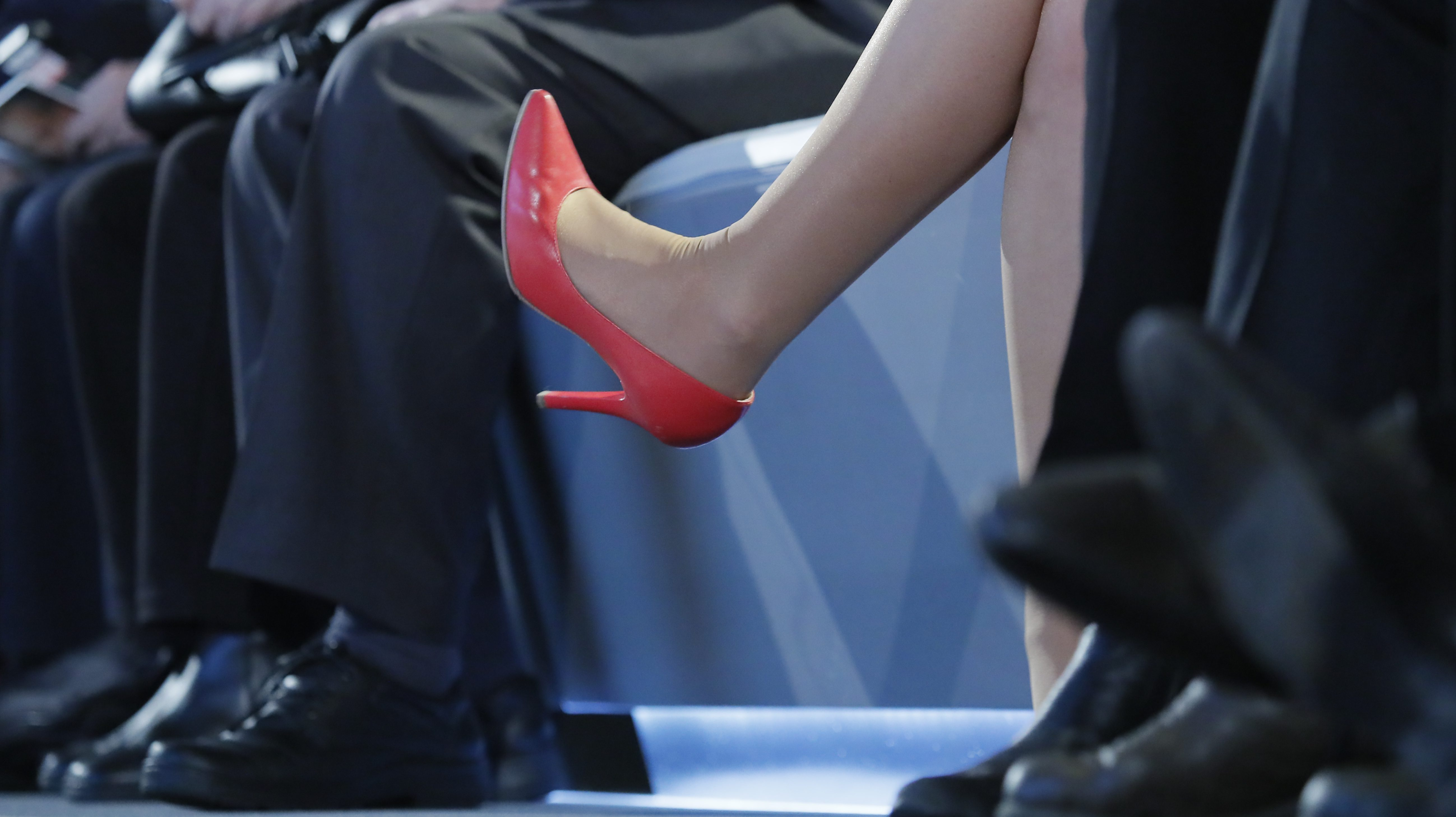 A woman wearing red heels sits among men wearing black pants and black shoes.
