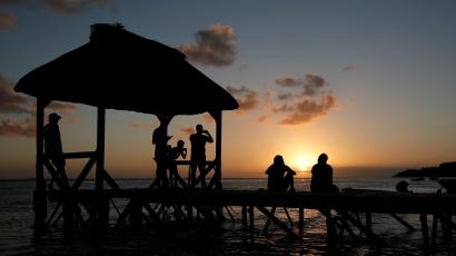 People look at the sunset from a beach in Mauritius