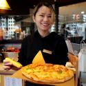 A waiter poses with a durian pizza at La Cesar Pizzaria in Shanghai