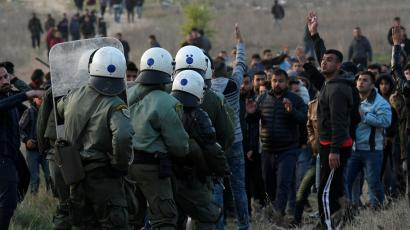 Riot police officers confront migrants and refugees in Greece