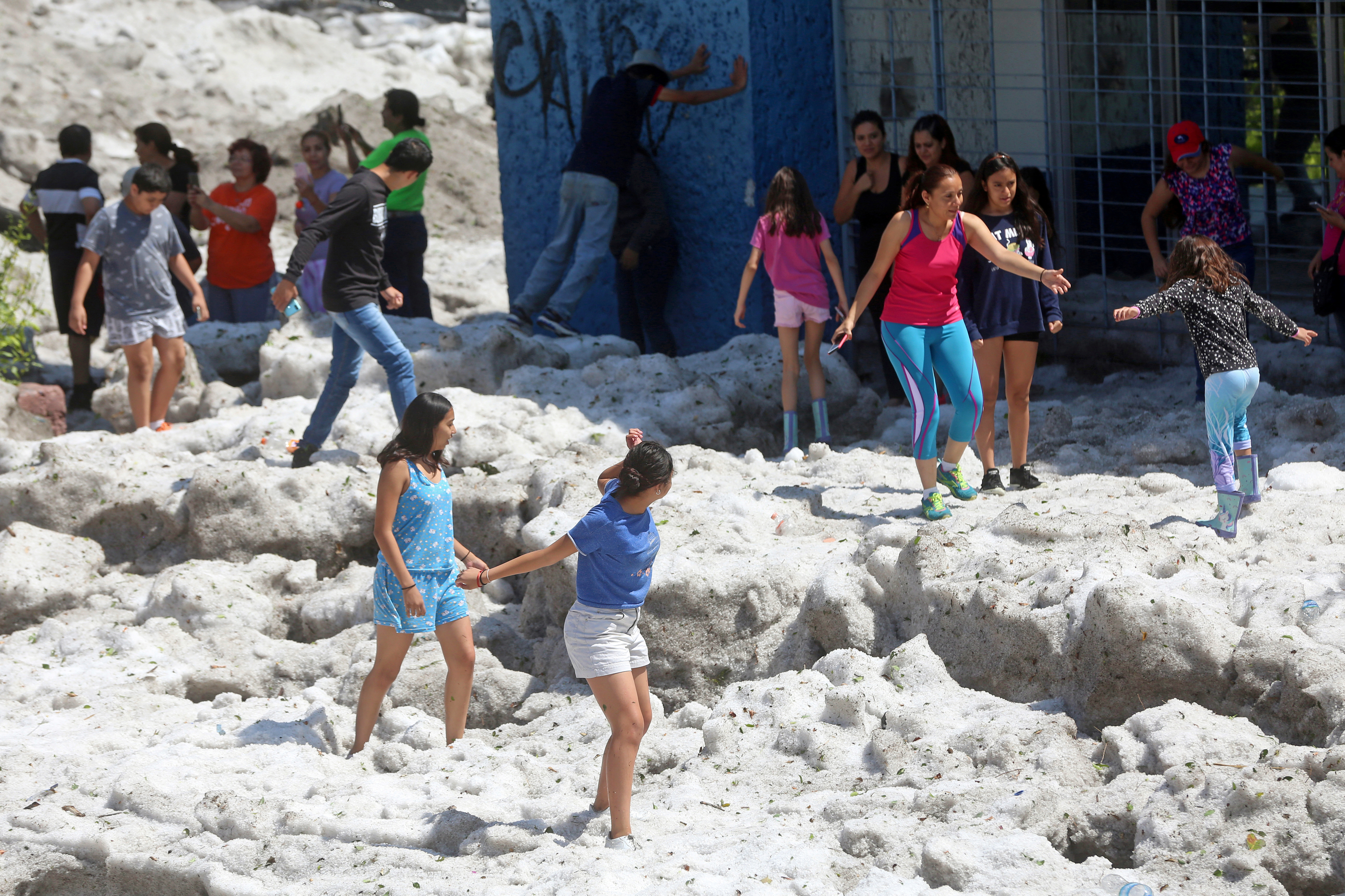 Residents play on top of ice after a heavy storm of rain and hail in Guadalajara