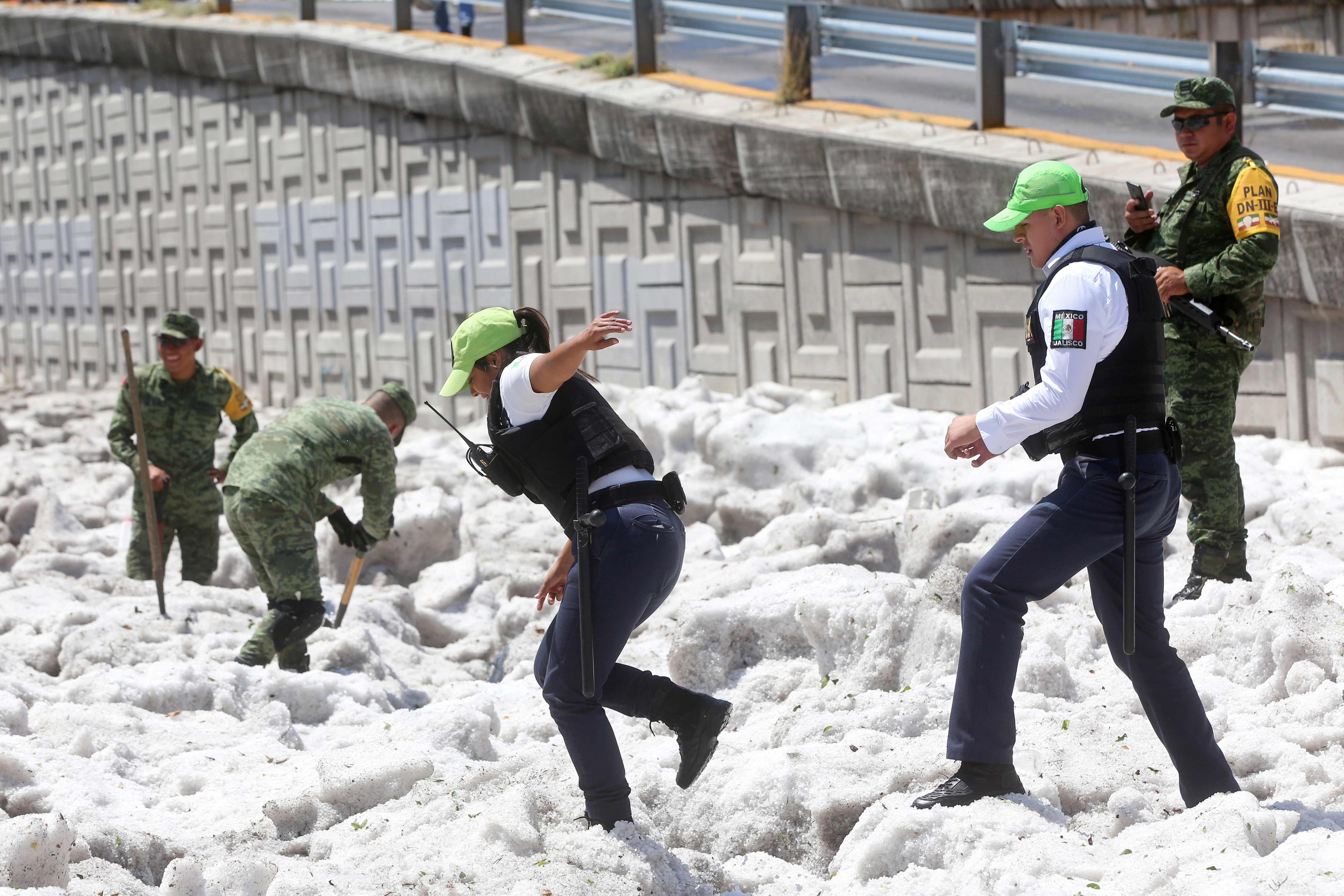 Security forces and soldiers try to clear away ice after a heavy storm of rain and hail in Guadalajara