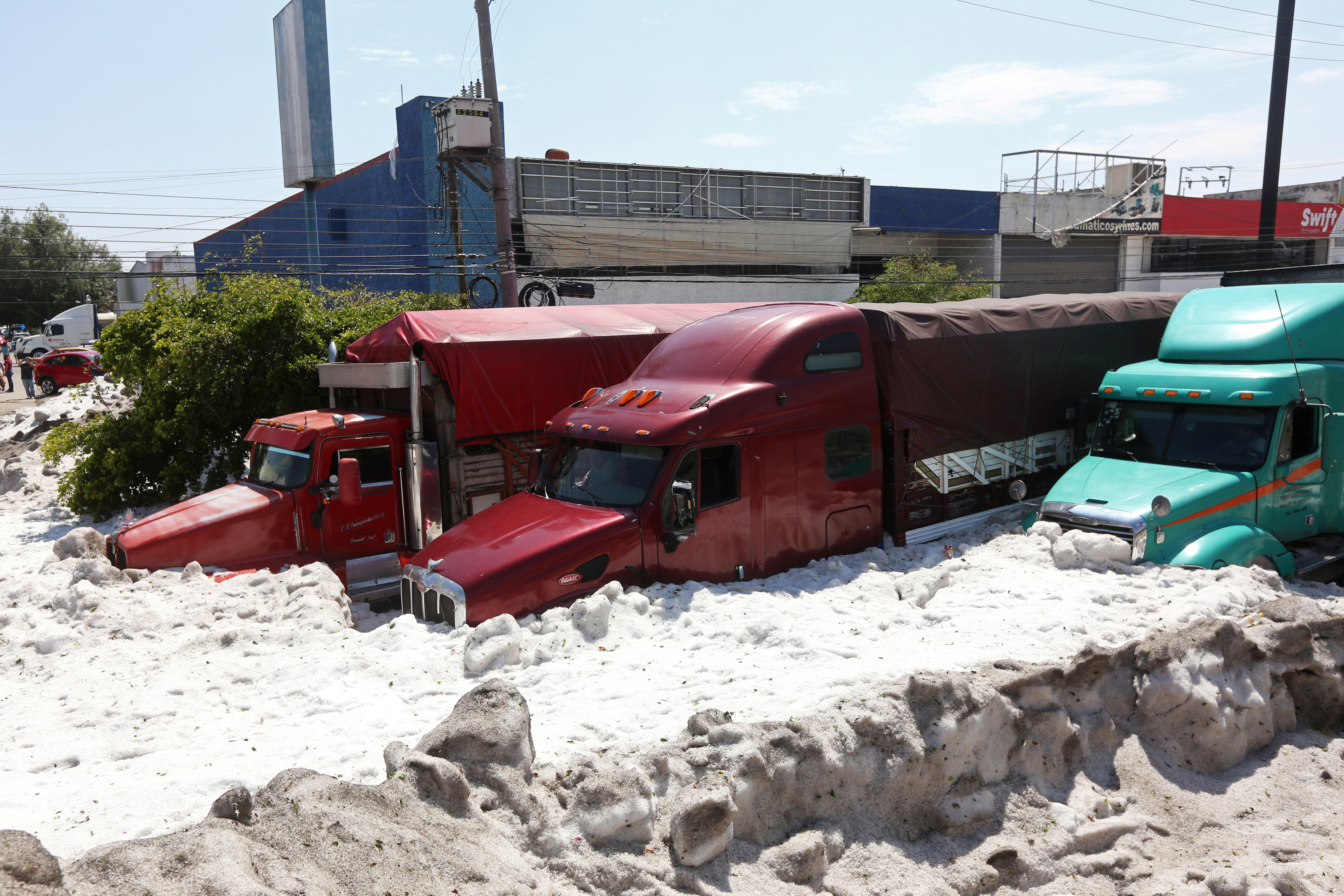 Trucks are buried in ice after a heavy storm of rain and hail which affected some areas of Guadalajara