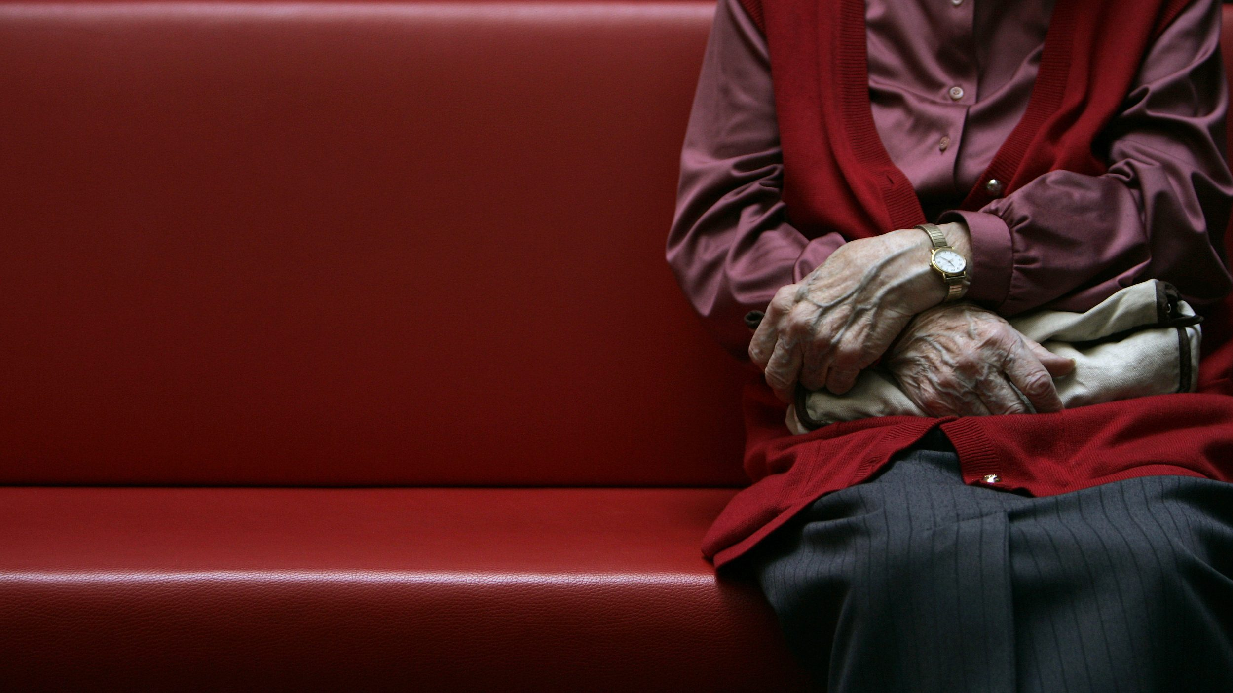 An image of a person sitting at the end of a Church pew