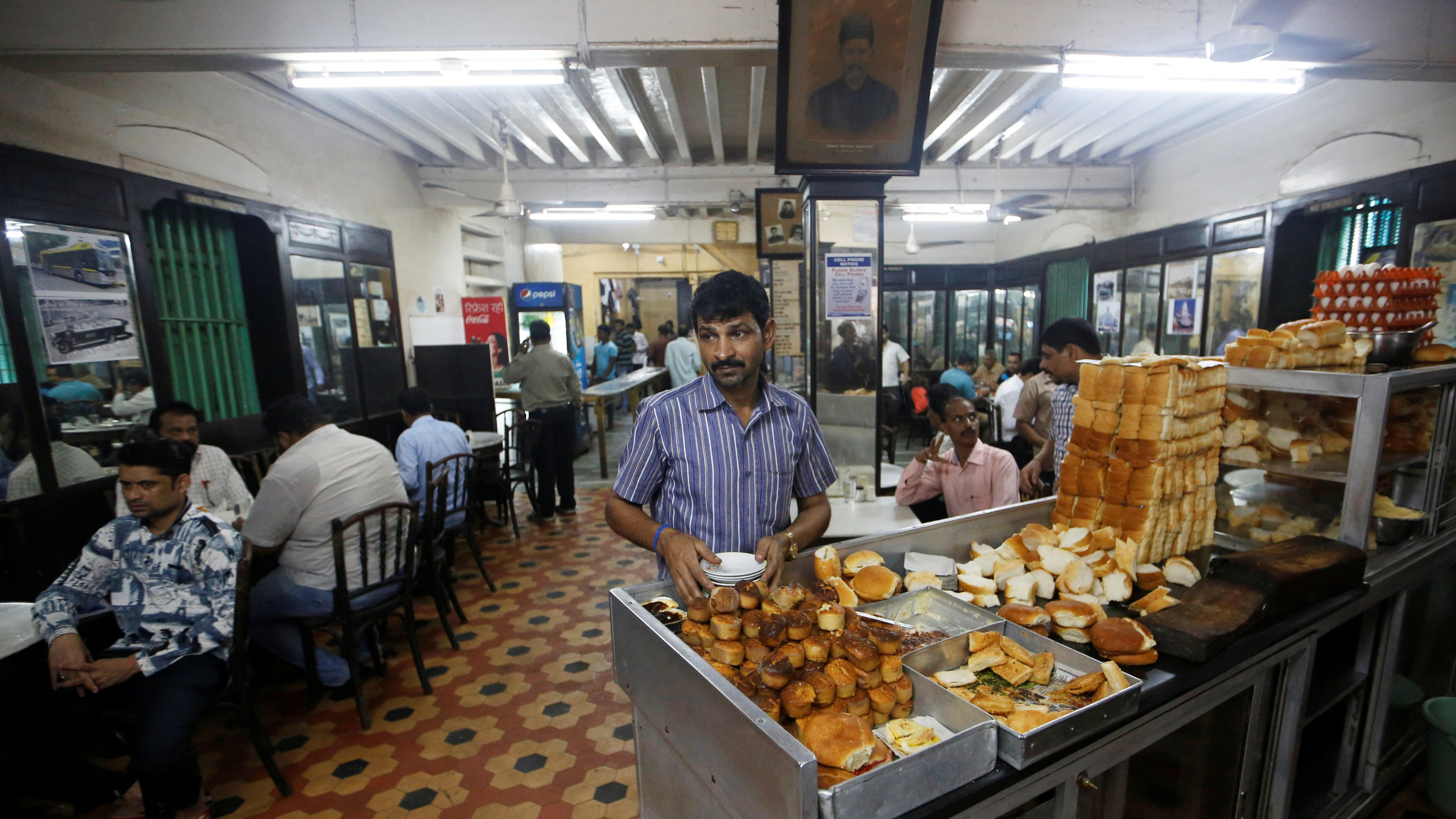 A waiter arranges plates at a counter stacked with breakfast items at an Iranian Parsi restaurant in Mumbai
