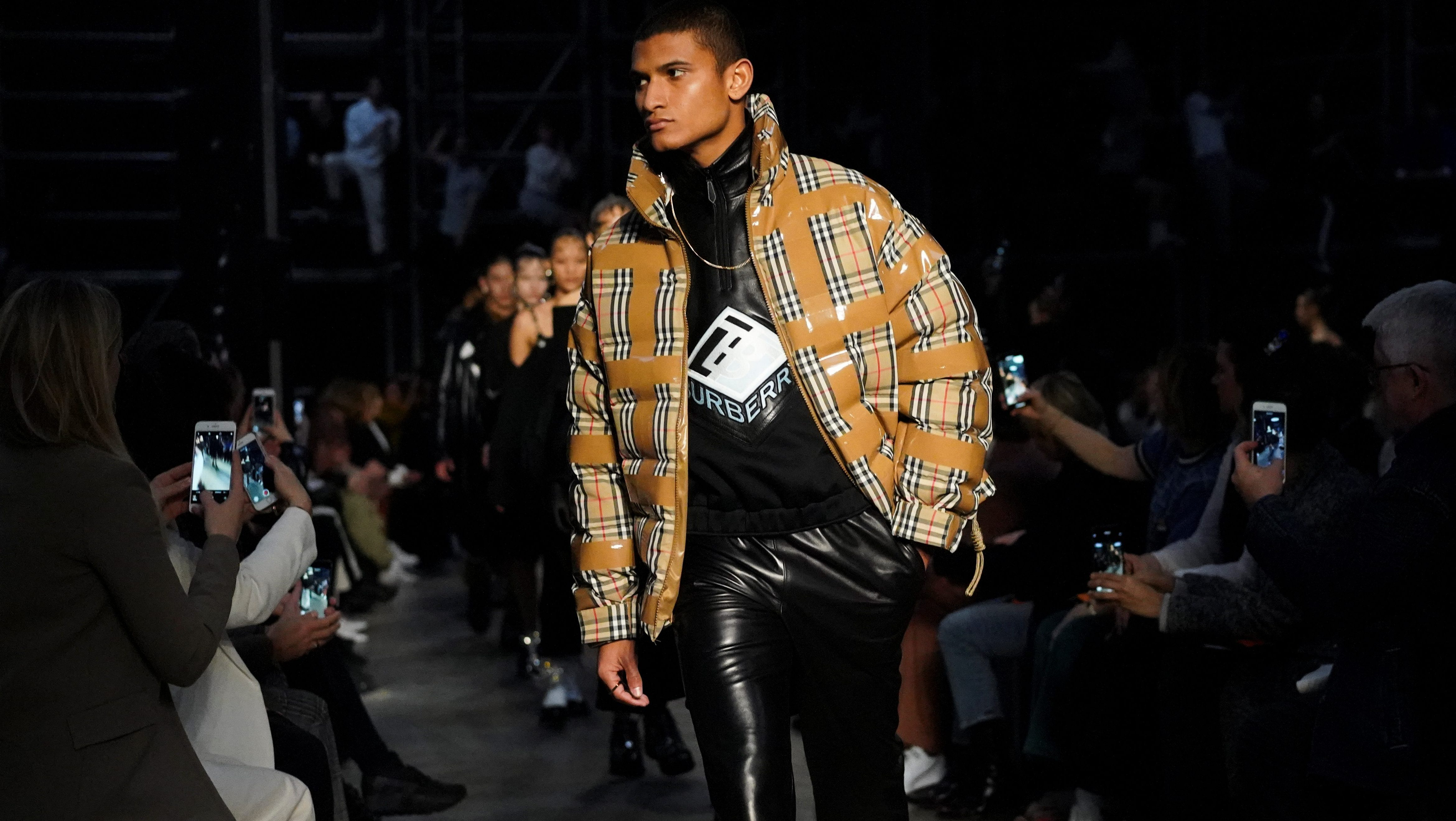 A male model walks the Burberry runway in a check puffer jacket.