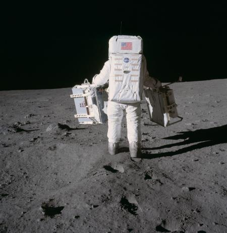 Buzz Aldrin carries scientific experiments on the surface of the moon.