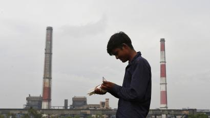 A boy examines a pigeon on a rooftop near a coal-fired power plant in New Delhi