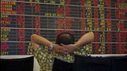 Thai investor sits in front of electronic board displaying live market data at stock broker's office in central Bangkok