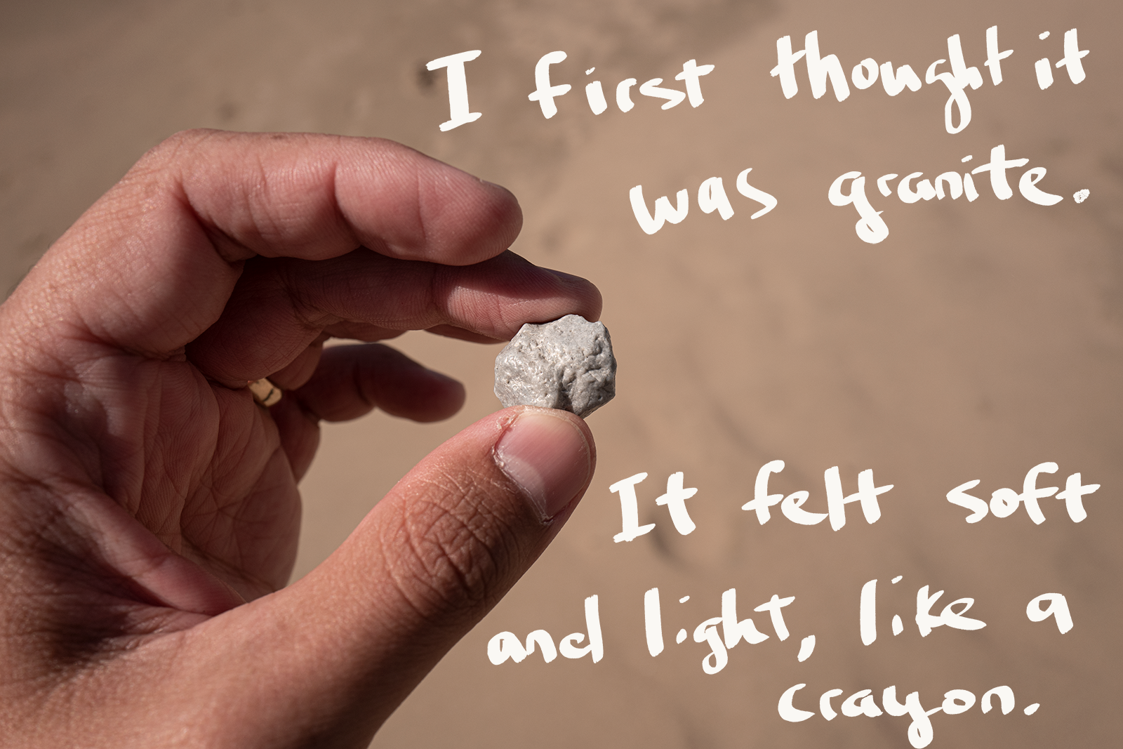 """An image of a hand holding a gray piece of what looks like a rock. There's handwriting on top of the photo that says: """"I first thought it was granite. It felt soft and light, like a crayon."""""""