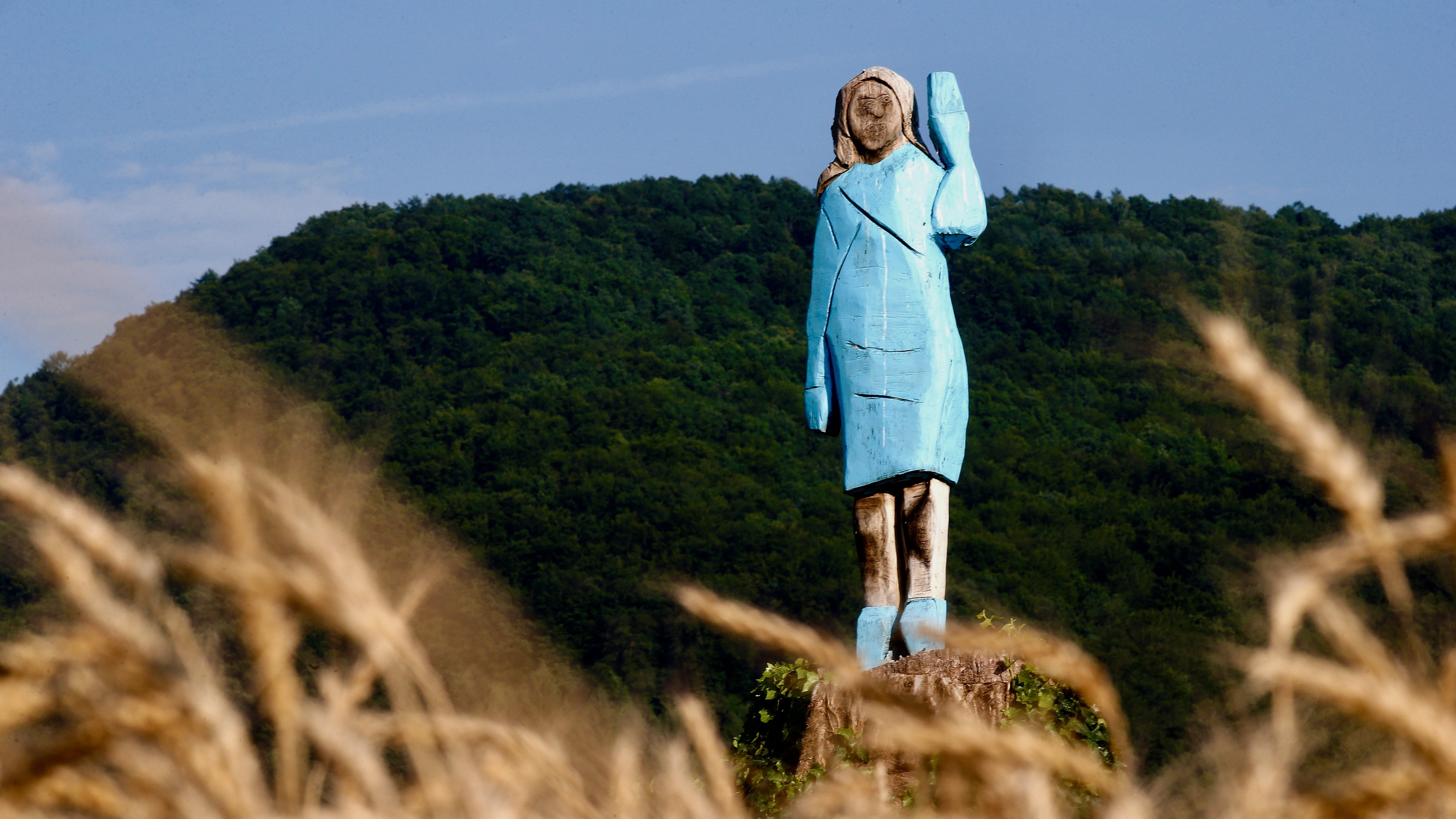 A crudely sculpted wooden sculpture of a woman wearing a light blue dress and waving with her left hand standing in a field with a green hill or mountain in the background