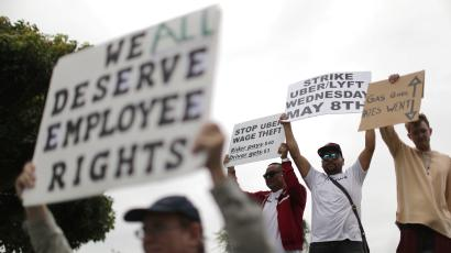 """An Uber driver holds a sign reading, """"We all deserve employee rights."""""""