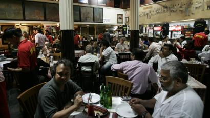 People are seen in the newly-reopened Cafe Leopold, a famous tourist restaurant and the scene of one of the first attacks last week, in Mumbai, India, Monday, Dec. 1, 2008. Mumbai returned to normal Monday to some degree, with many shopkeepers opening their doors for the first time since the attacks began. As authorities finished removing bodies Monday from the bullet and grenade-scarred Taj Mahal hotel, a Muslim graveyard refused to bury nine gunmen who terrorized this city over three days last week, leaving at least 172 people dead and wreaking havoc at some of its most famous landmarks. (AP Photo/Lefteris Pitarakis)