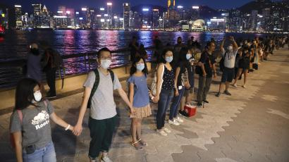 """Demonstrators link hands as they gather at the Tsim Sha Tsui waterfront in Hong Kong, Friday, Aug. 23, 2019. Demonstrators were planning to form 40 kilometers (25 miles) of human chains Friday night to show their resolve. They said the """"Hong Kong Way"""" was inspired by the """"Baltic Way,"""" when people in the Baltic states joined hands 30 years ago in a protest against Soviet control."""
