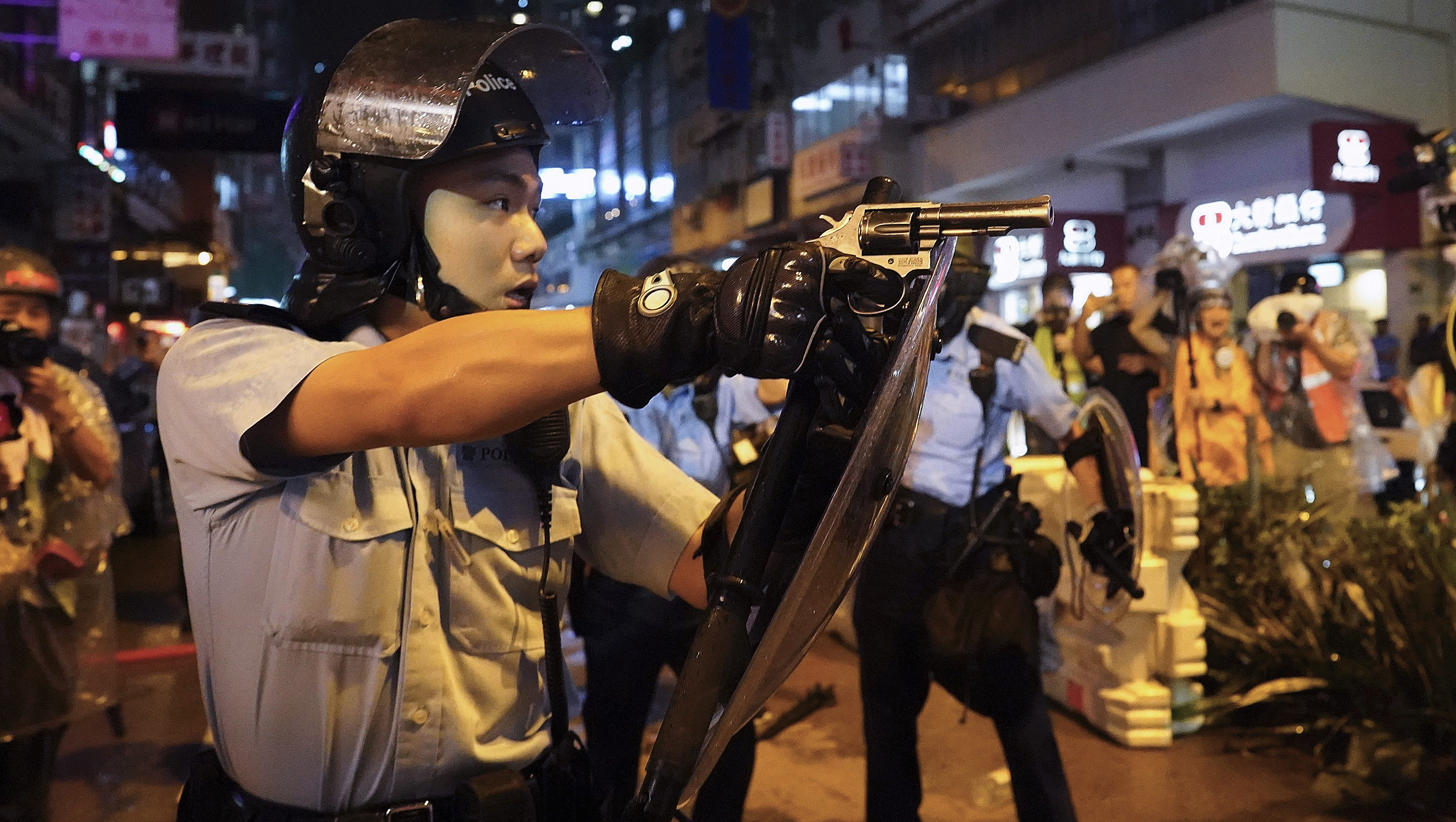 Hong Kong police officer points gun at protesters