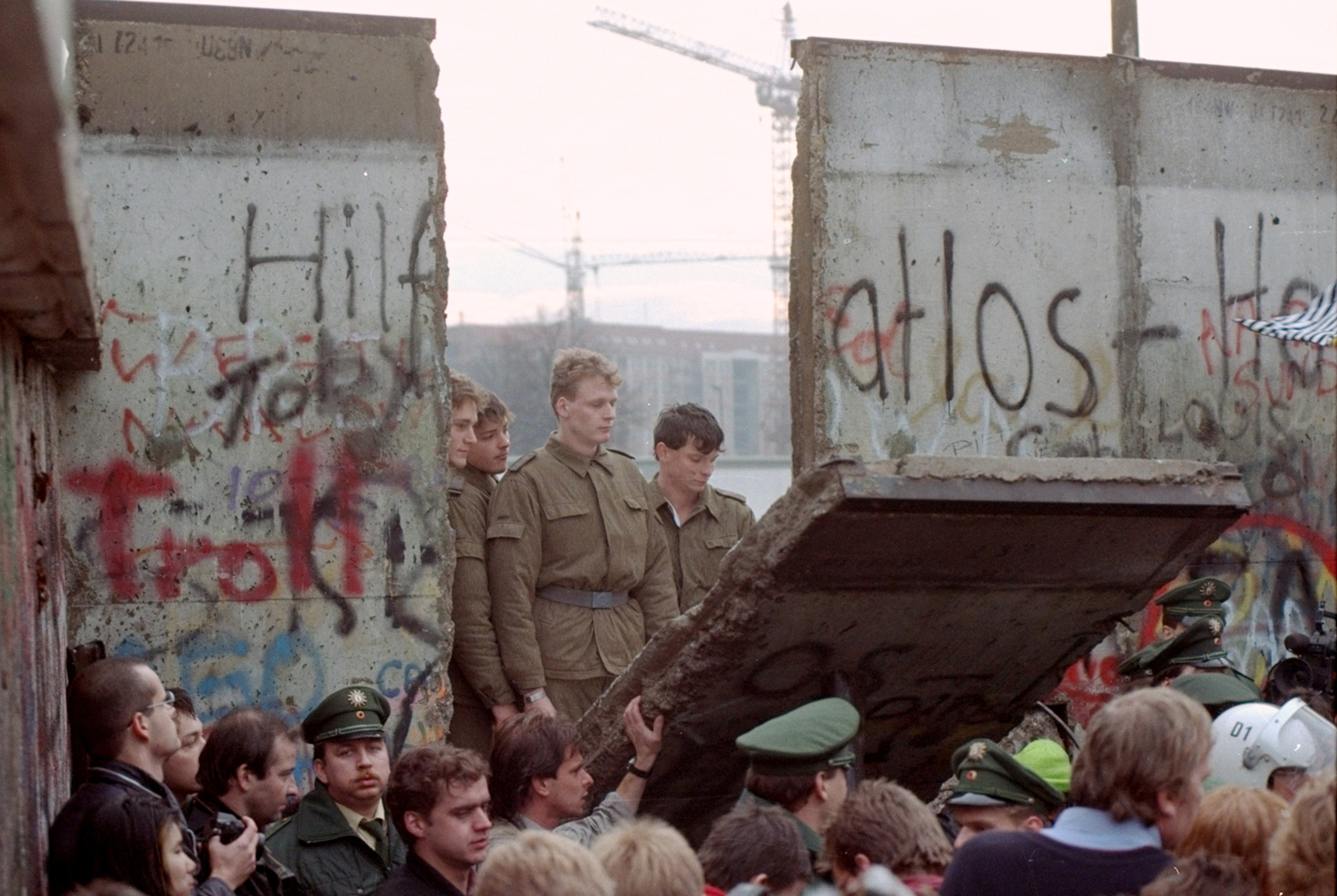 FILE - In this Nov. 11, 1989 file photo, East German border guards are seen through a gap in the Berlin wall after demonstrators pulled down a segment of the wall at Brandenburg gate, Berlin. The Berlin Wall is gone, but people can still tag their memories upon it online. The Berlin Twitter Wall, which went online Tuesday, Oct. 20, 2009 encourages people to share their memories of the wall's collapse and hopes for the future on a scrolling wall using Twitter, the social networking site.