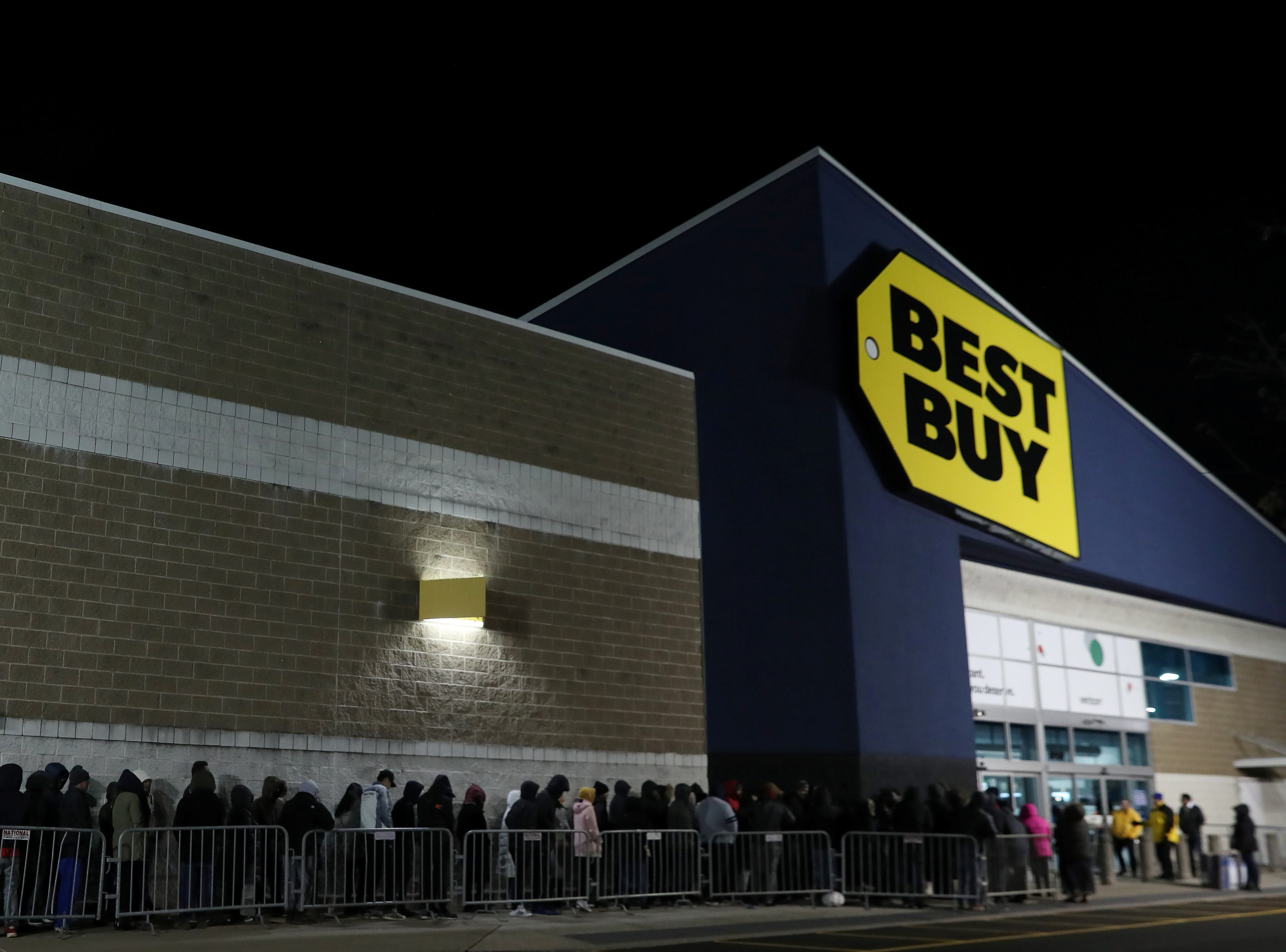 People wait in line to shop at Best Buy