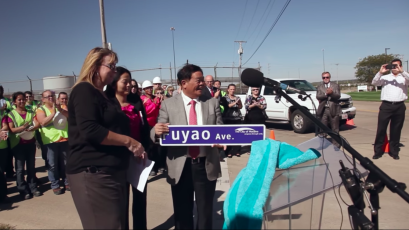 Cao Dewang, founder of Fuyao, accepts a road sign named after Fuyao glass in the US.