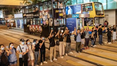 Proteters form a A human chain in front of bus and tram traffic in Hong Kong