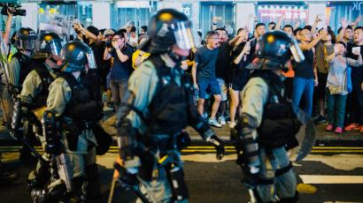 Locals shout at riot police as they chase anti-government protesters down Nathan Road in Mong Kok in Hong Kong.