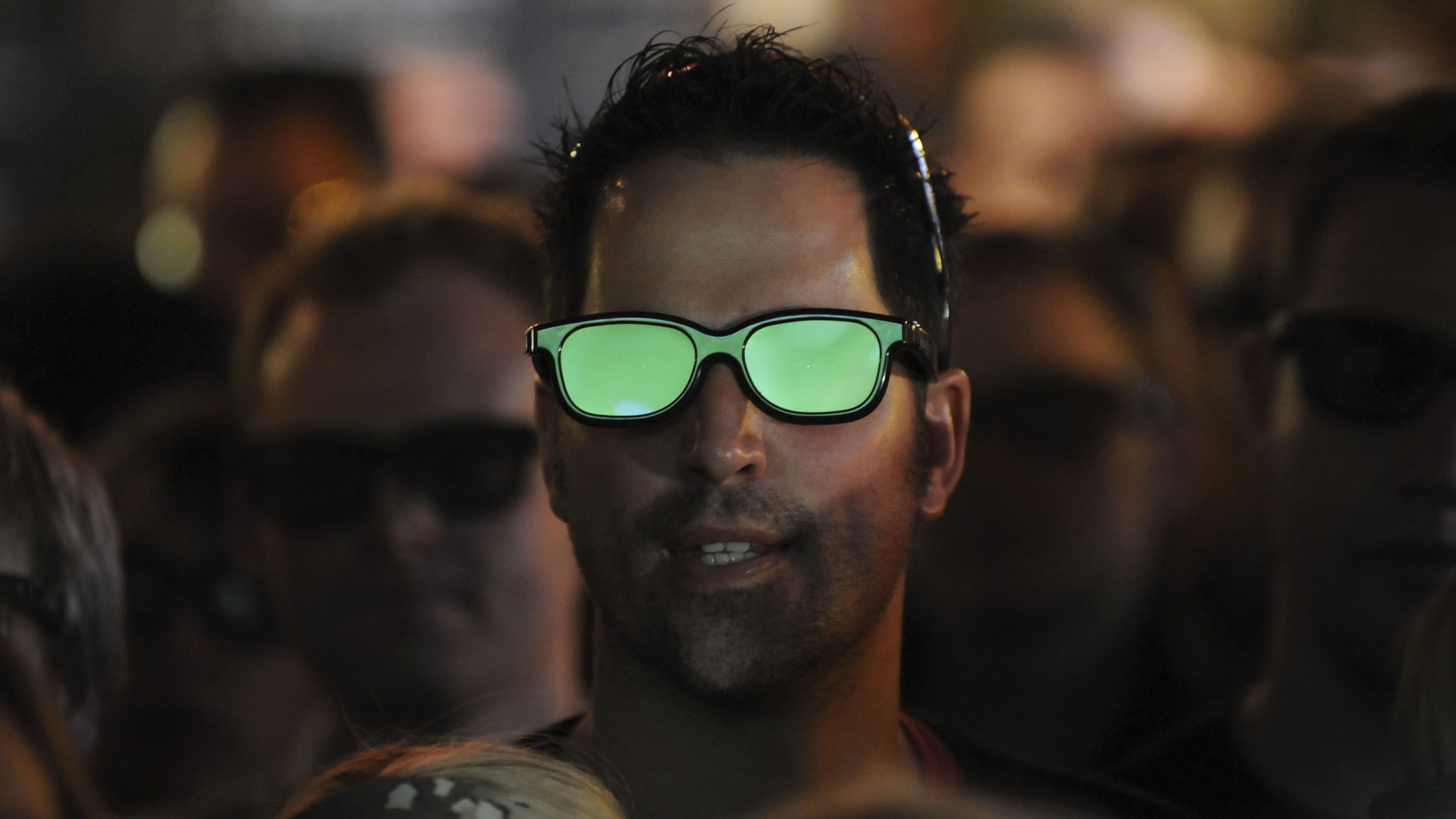 The pitch is reflected in a football fan's 3D glasses as he watches a live 3D TV football match in a pub in London