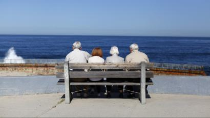 A pair of elderly couples view the ocean and waves