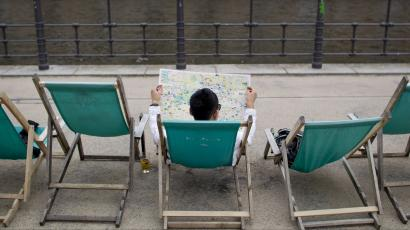 Tourist reads Berlin city map as he sits in deck chair at river Spree embankment in Berlin