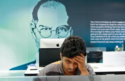 An employee works on a computer terminal against the backdrop of a picture of late Apple co-founder Jobs at the Start-up Village in Kinfra High Tech Park in Kochi