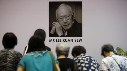 People bow in front of a coffee of Lee Kuan Yew