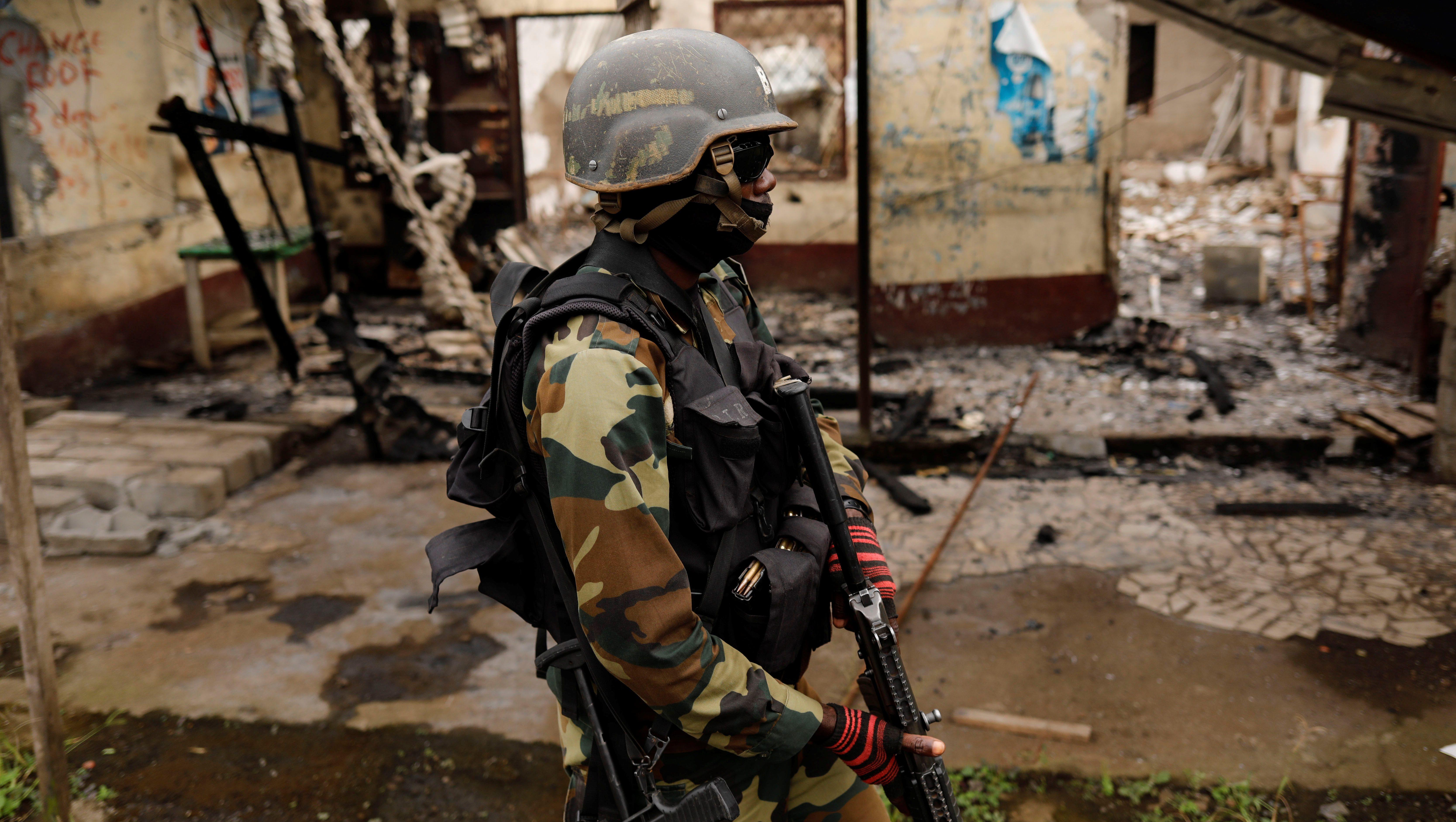 A Cameroonian elite Rapid Intervention Battalion (BIR) member patrols the abandoned village of Ekona near Buea in the anglophone southwest region, Cameroon