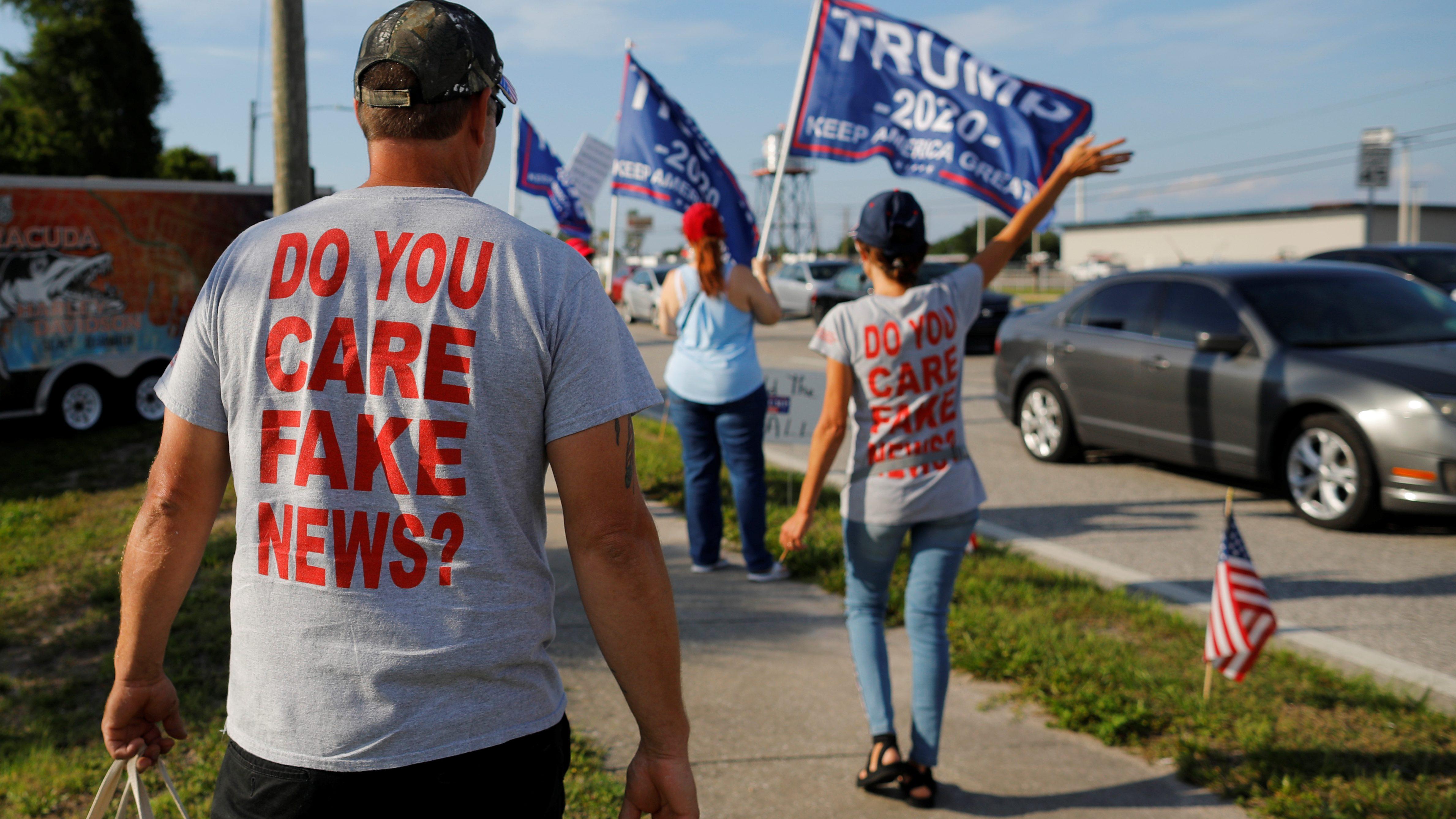 A man wears a t-shirt saying Do you care, fake news?