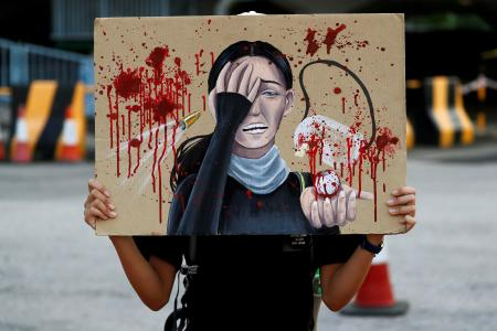 A student holds a placard honouring the woman that was shot in the eye at a protest, during a rally to call for political reforms outside City Hall in Hong Kong, China, August 22, 2019.