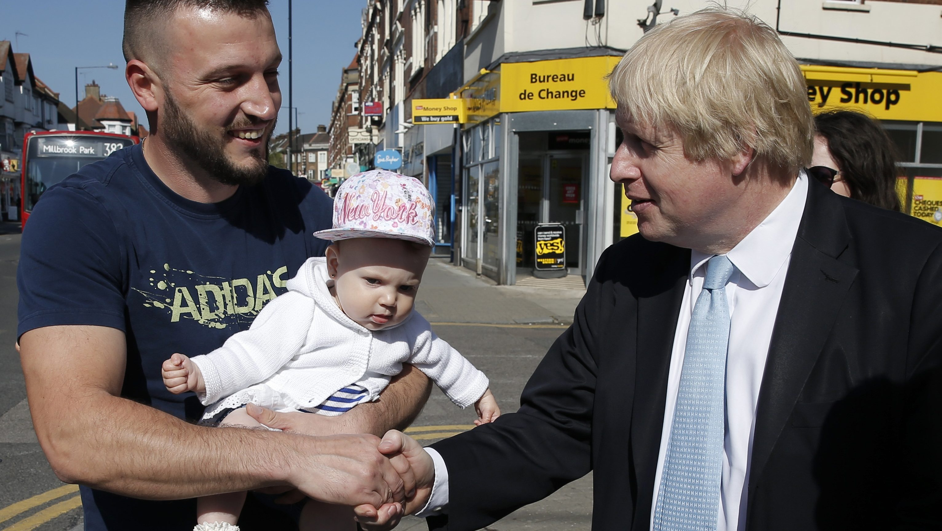 London's Mayor Boris Johnson greets a man with a baby whilst campaigning for the local Conservative candidate in Finchley, north London, April 21, 2015.