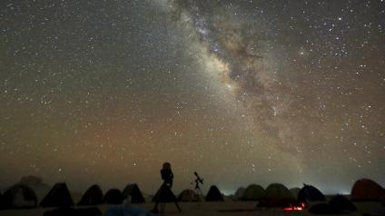 The 'Milky Way' is seen in the night sky around telescopes and camps of people over rocks in the White Desert north of the Farafra Oasis southwest of Cairo