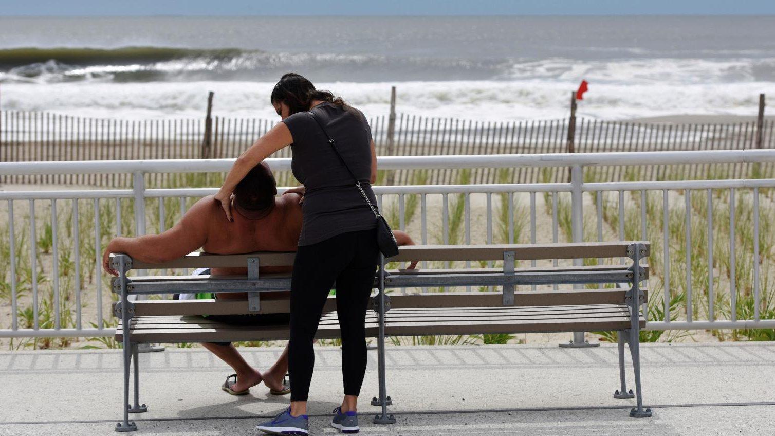 A woman rubs a man's shoulders