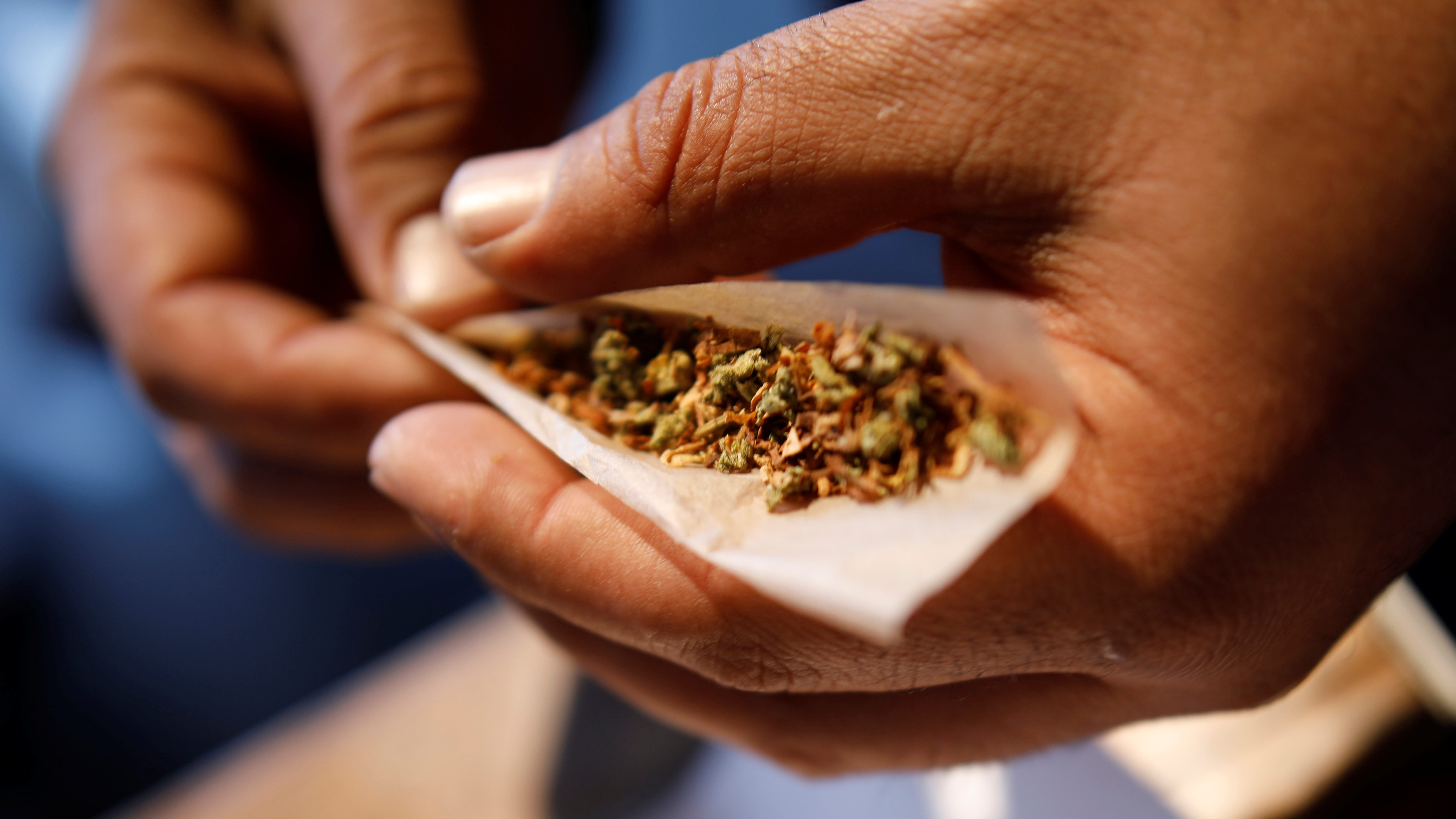 A man prepares a cigarette mixed with marijuana during Cannatech 2017, an annual global cannabis industry event, in Tel Aviv, Israel