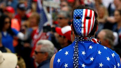 A pro-Trump rally participant wears a U.S. flag during the Southern California Make America Great Again march in support of President Trump, the military and first responders at Bolsa Chica State Beach in Huntington Beach, California