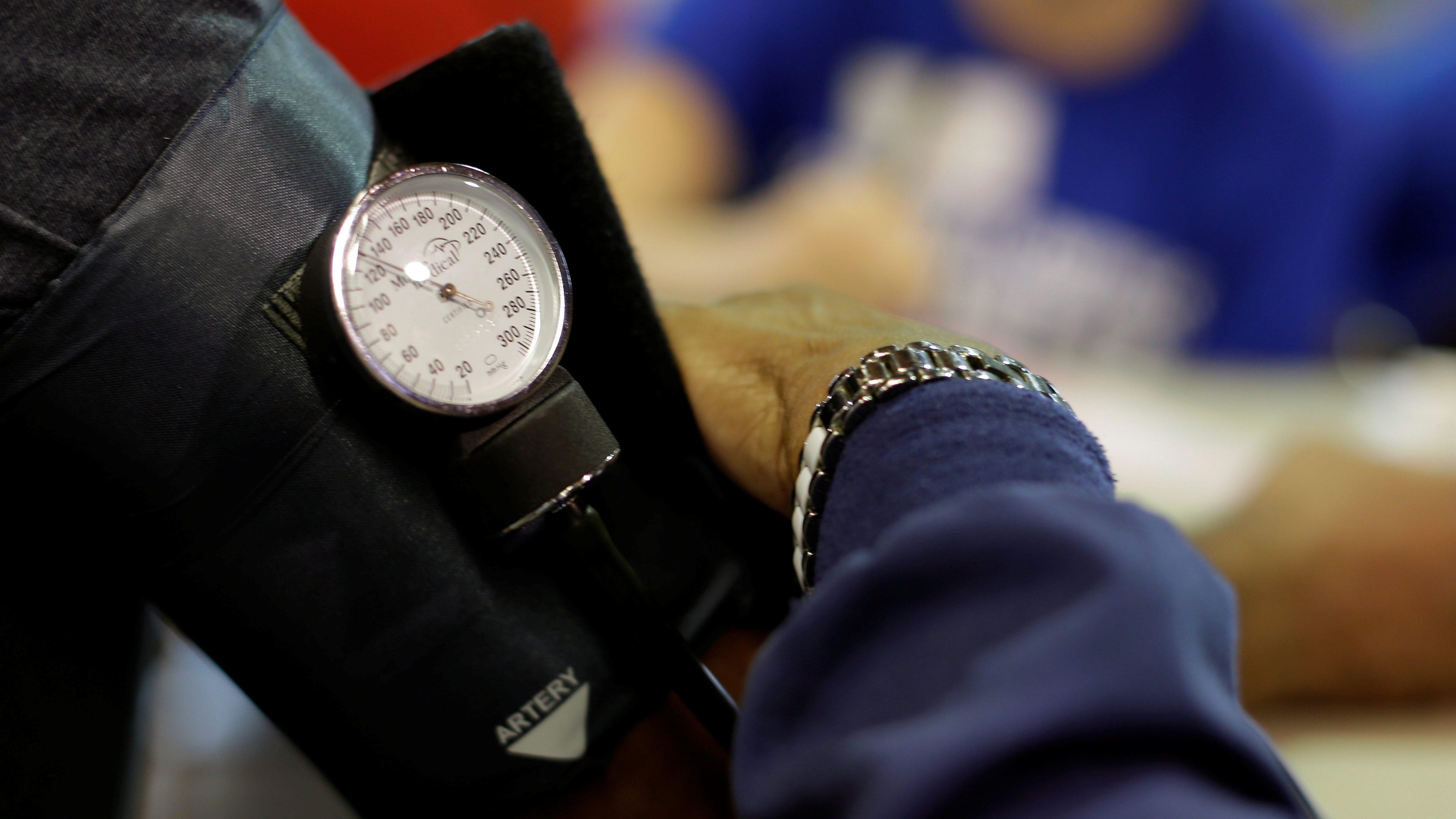 A man's arm in a blood pressure cuff
