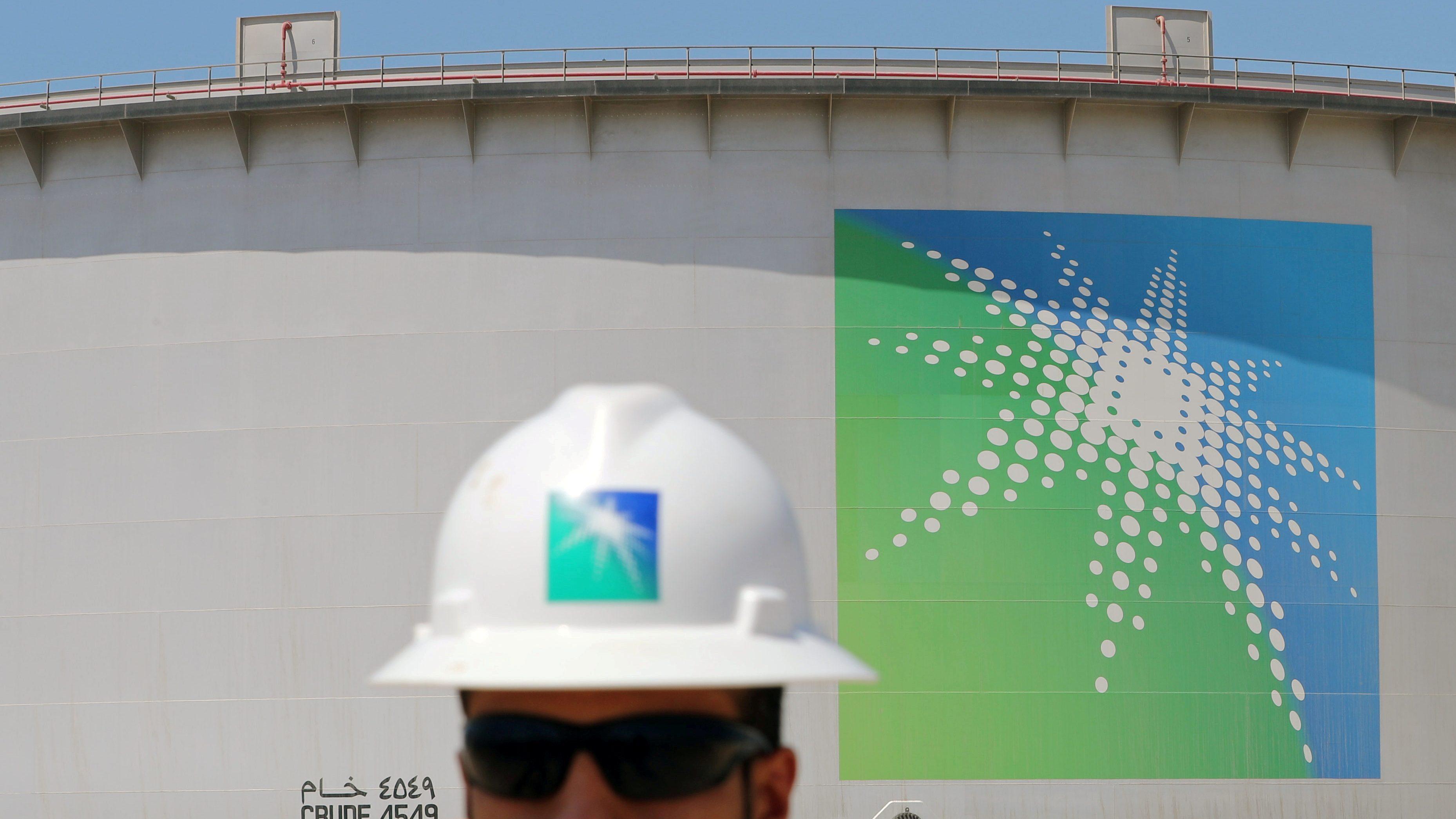 An Aramco employee walks near oil tank at Saudi Aramco's Ras Tanura oil refinery and oil terminal in Saudi Arabia May 21, 2018. Picture taken May 21, 2018.
