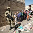 Residents look on while police patrol as South African President Cyril Ramaphosa visits crime ridden Hanover Park to launch a new Anti-Gang Unit, in Cape Town